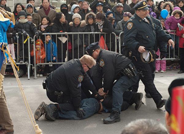 除了在中國大陸繼續推行對法輪功的迫害政策,周永康還將迫害政策輸送到海外。圖為2011年2月12日,在紐約法拉盛新年遊行慶祝活動中,一華裔男子從觀眾群中衝到法輪功隊伍的前面,拉扯橫幅並折斷橫桿。三個警察立即衝上去將其制服並逮捕。(大紀元)