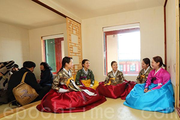 外国游客穿上韩服,坐在韩国的暖炕上体验著韩国特有的生活韵味。(摄影:全宇/大纪元)
