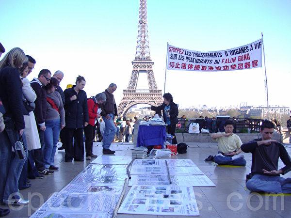在世界各國的著名景點及繁華地帶都能見到法輪功學員義務在講真相。圖為到法國巴黎,遊客在法輪功真相點上了解中共迫害法輪功真相。(大紀元)