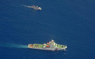 南中國海局勢再度緊張升級。中共軍艦7月3日在爭議水域扣押6名越南漁民和一艘越南QNg94912 TS號漁船。圖為3月29日,中方一艘海上警衛船(下)與越南一艘物資船在南海對峙。(JAY DIRECTO/AFP)