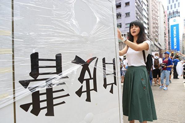 2014年7月1日,香港市民無懼恐嚇,紛紛走上街頭,用和平有秩序的方式,抗議中共亂港破壞一國兩制,要求特首梁振英下台。圖為遊行民眾將大型白皮書道具倒放表達抗議。(余鋼/大紀元)