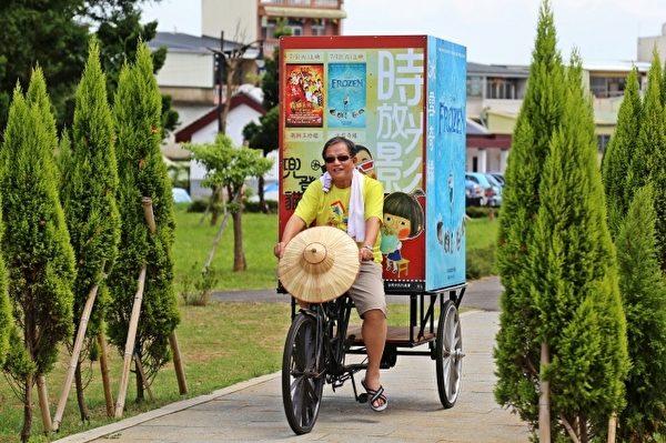 苗栗市長邱炳坤騎乘電影廣告三輪車,邀請鄉親來看電影。(苗栗市公所提供)