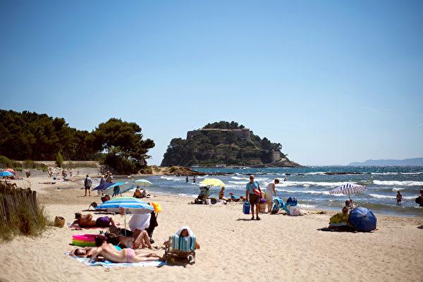 游客在法国布雷冈松堡旁的Cabasson海滩做日光浴。(BERTRAND LANGLOIS/AFP)