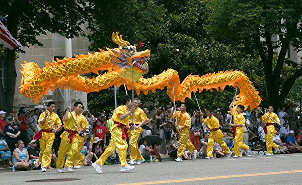 法轮功参加美国首都华盛顿DC的独立日庆祝游行,其中由13名法轮功学员组成的舞龙队,在现场有如一条黄色巨龙在穿梭飞腾,成为当日游行中的亮点。(李莎/大纪元)