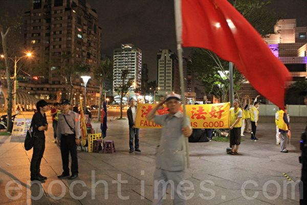 在台北101大樓前靜坐的法輪功學員及旁觀民眾長期遭受愛國同心會辱罵、恐嚇甚至霸凌。圖為日前法輪功學員參與活動時,愛國同心會成員揮舞紅旗騷擾。(大紀元)