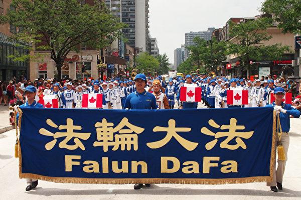 加拿大国庆日游行队伍中,最引人注目的当属这支由100多名法轮功学员组成的天国乐团。不少观众甚至是专程前来观看这个身着蓝白色中国传统服饰的军乐队游行队伍。(Nathalie Dieul/大纪元)