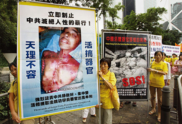 香港遊行隊伍中展示黑龍江省法輪功學員王斌在勞教所被警察殘暴毒打致死、器官被摘的真相。(AFP)