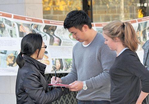 法輪功學員在澳洲悉尼北岸繁華地區車士活(Chatswood)市中心的維多利亞主街舉辦「真相長城」活動。澳洲市民正在徵簽表簽名,正義發聲,制止中共活摘法輪功器官的惡行。(明慧網)