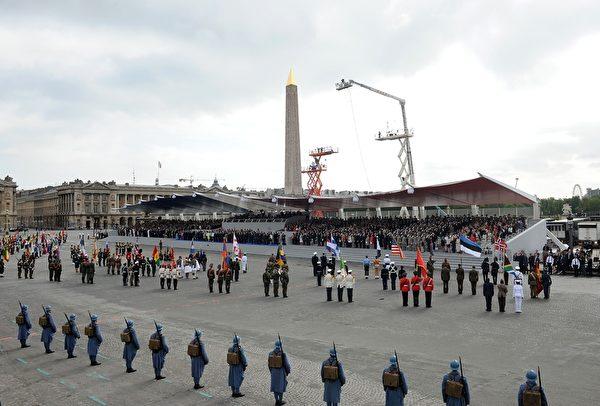 手执各国国旗的士兵们汇集到协和广场的主席台前。(Antoine Antoniol/Getty Images)