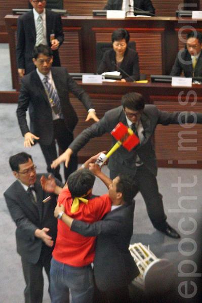 香港特首梁振英7月15日向中共人大常委會提交啟動政改的咨詢報告,社民連議員梁國雄在立法會會議上向政務司司長林鄭月娥抗議。(潘在殊/大紀元)