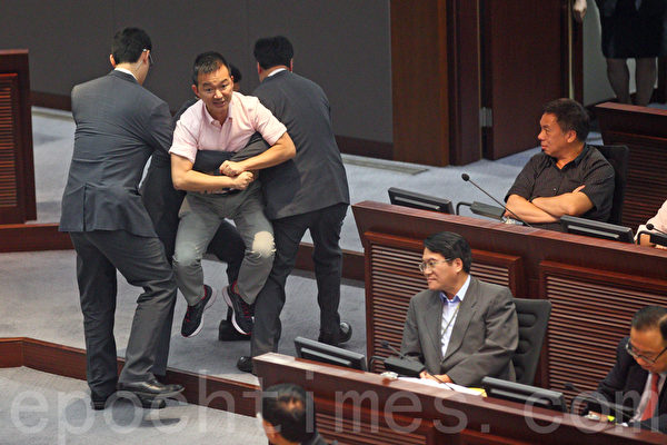 香港特首梁振英7月15日向中共人大常委會提交啟動政改的咨詢報告,人民力量議員陳志權在立法會會議上抗議報告漠視民意,被保安抬走。(潘在殊/大紀元)