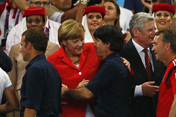 世界杯结束后,德国总理默克尔向德国队主教练勒夫祝贺。(Clive Rose/Getty Images)