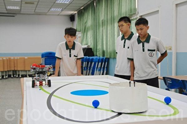 国中竞赛组第一名的三位男生在教室操作机器人,他们分别是:林翌志(中)、方翰毅(左1)、陈昱廷(右1)。(许享富 /大纪元)