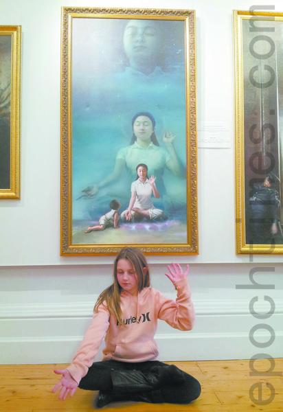 澳洲女孩何莉坐在《純淨入仙境》畫作前,模仿著畫中女修煉者的姿勢打手印,家人很高興,一家人表示要去煉功點學功。(攝影:李梅/大紀元)
