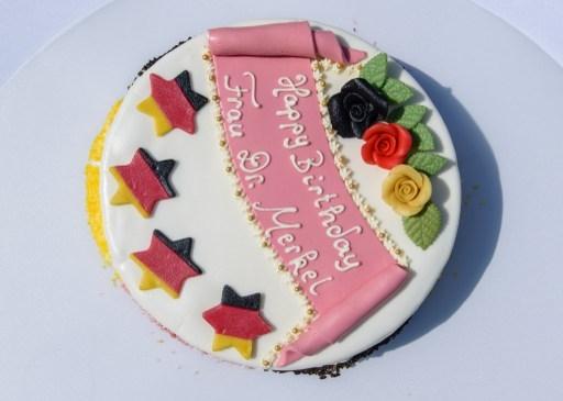 送给默克尔的蛋糕,上面有四颗星,显然是庆祝德国足球队第四次获得世界冠军。蛋糕上还写着:生日快乐!默克尔博士女士。 (CLEMENS BILAN / AFP)