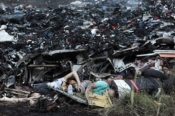 马航MH-17班机7月17日疑遭飞弹击落,机上298名乘客及机组人员全数罹难。图为失事现场一片狼藉,飞机残骸及罹难者遗体、遗物四处散落。(DOMINIQUE FAGET/AFP/Getty Images)