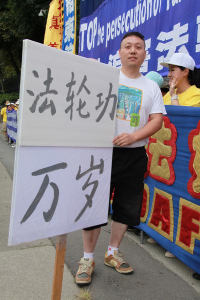 """图:大陆移民王先生自已制作了一个一人高的牌子,上面写着""""法轮功万岁""""。他认为法轮功是全球华人中最优秀的团体。(田园/大纪元)"""