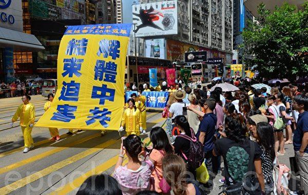 適逢法輪功7.20反迫害15年活動,來自各國的逾九百名法輪功學員在香港北角英皇道遊行到政府總部,呼籲全球制止中共迫害和停止活摘器官,吸引許多民眾觀看。(宋祥龍/大紀元)