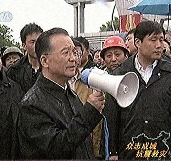 由于江泽民的阻挠,中共军队并不听从温家宝的指挥与调度进行救灾。图为5月13日温探访汶川灾区。(AFP)