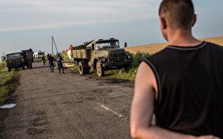 2014年7月19日,在格拉波夫(Grabovo)马航MH17失事现场,当亲俄叛军控制现场后,一名人员阻止他人进入,急救人员将尸体搬上卡车。美国国务卿克里20日抨击俄及亲俄叛军需为MH17失事负责。(Brendan Hoffman/Getty Images)