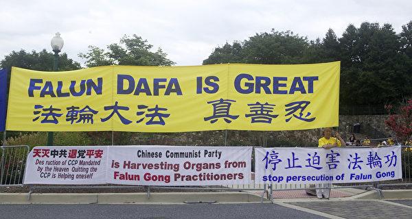 華府法輪功學員在中使館前打橫幅,抗議15年來中共對法輪功學員的迫害。(攝影:奚明/大紀元)