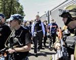 7月21日,歐洲安全及合作組織首席監察員Alexander Hug(中)與荷蘭專家,進入親俄烏克蘭叛軍控制的MH17航班失事現場,並靠近裝有遇難者遺體的冷藏車廂。(BULENT KILIC/AFP)