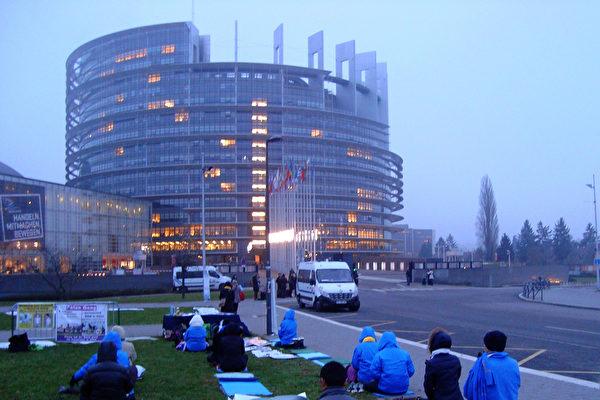 2013年12月12日傍晚,法輪功學員在法國東部的斯特拉斯堡歐洲議會大廈前和平請願。當天,歐洲議會通過了反活摘器官的議案。八天後的12月20日,李東生被調查;12月25日,迅即被免職。(黎平/大紀元)