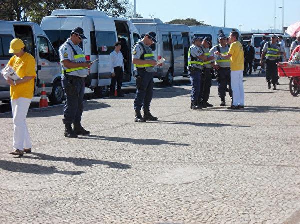 7月16日,中共保安指使巴西警方阻擋法輪功學員靠近習近平車隊,法輪功學員們給警察們發放真相資料。警察們仔細閱讀,中共保安束手無策。(大紀元)
