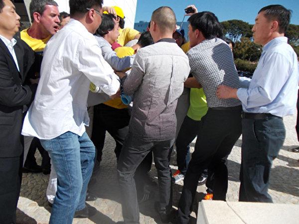 7月17日,中共爪牙於公共場合無理阻擋法輪功學員行動,搶走橫幅,圍毆學員。(大紀元)