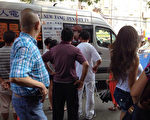 """新唐人电视台推广车在法拉盛卡辛那大道中美超市附近推广时,重播了《今日大纽约》多集""""红色势力渗透法拉盛""""系列新闻报导,吸引了很多市民驻足围观。(新唐人推广组提供)"""