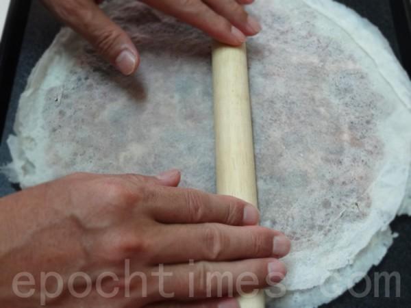 再蓋上另張潤餅皮或春捲皮後捍平、壓緊邊緣、蝦餅戳洞。(攝影:彩霞/大紀元)
