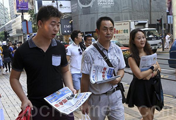 周永康落網次日,在尖沙咀廣東道一帶,手拿《大紀元時報》的遊客比比皆是,人們街頭巷尾地議論中國局勢。(余鋼/大紀元)