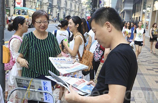 周永康落網次日,在尖沙咀廣東道一帶,準確預測周永康下台的香港大紀元受歡迎,市民遊客爭相搶閱。(余鋼/大紀元)