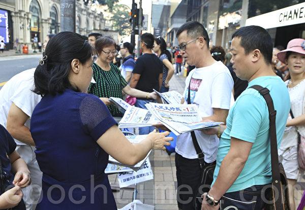周永康7月29日被中紀委宣佈立案審查,7月30日香港大紀元三個版重點報導周永康下台內幕,市民遊客爭相搶閱。圖為尖沙咀廣東道一帶。(余鋼/大紀元)