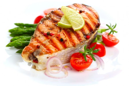 Grilled salmon with lime, asparagus and cherry tomatoes on white