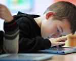 """互联网问世造就了""""数码原生代""""(digital natives),这些出生于科技时代,熟悉且生活在充满数码科技产品时代的小孩,对智能手机和平板电脑的知识与应用远远超过大人。 (FREDERICK FLORIN/AFP/Getty Images)"""