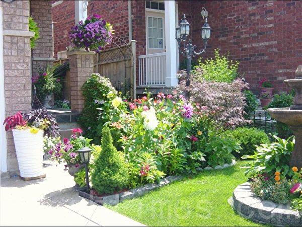 这是爱养花的人家,边边角角都种满了花,五彩缤纷的花长得很旺盛,花池、草地整理的得很整齐。(李文笛 /大纪元)