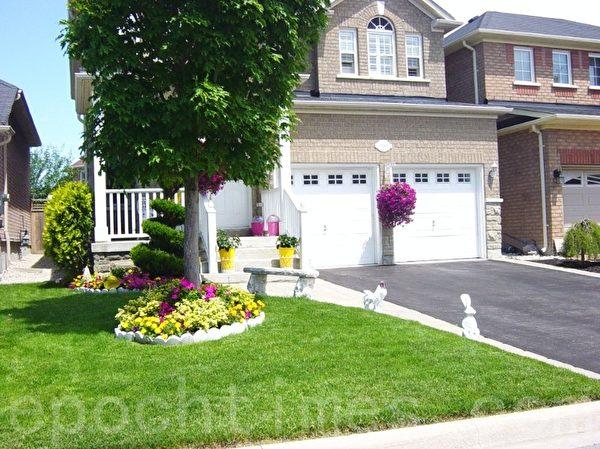 几个可爱的小工艺品、螺旋状的松树,车库的吊花,加上地上各色花,看上去门前很生动活跃。(李文笛 /大纪元)