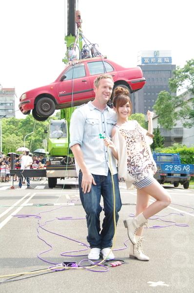 主持人提姆蕭、翁滋蔓於2014年8月9日在台北參與舉辦大型街頭科學實驗秀。利用小型吸塵器將汽車吊上空中。(黃宗茂/大紀元)