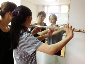 老师教蕙泽调整吹长笛的姿势。(建传音乐教室提供)