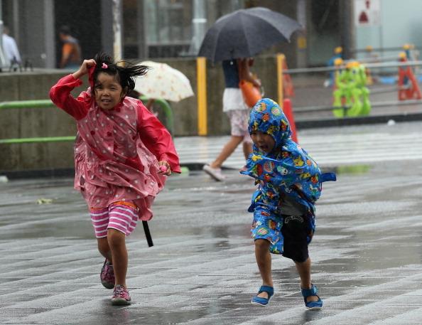 2014年8月10日,日本兵庫縣姬路城的兩名兒童在颱風吹襲下,吃力的前進。(Buddhika Weerasinghe/Getty Images)