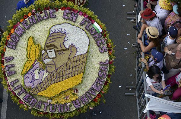 2014年8月10日,哥伦比亚鲜花节,花农们背着精心制作的花盘游行,花盘图案描绘已故的哥伦比亚作家加夫列尔·加西亚·马尔克斯。(Raul ARBOLEDA/AFP)