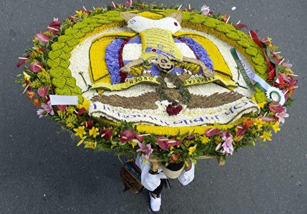 2014年8月10日,哥伦比亚鲜花节,花农们背着精心制作的花盘游行,花盘图案描绘哥伦比亚国家足球队球员詹姆斯·罗德里格。(Raul ARBOLEDA/AFP)