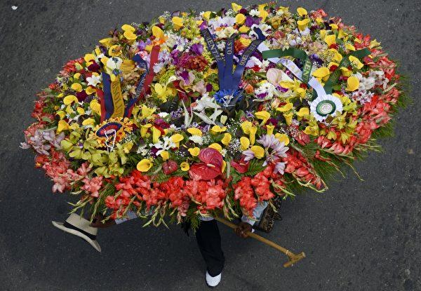 2014年8月10日,哥伦比亚鲜花节,花农们背着精心制作的花盘游行。(Raul ARBOLEDA/AFP)