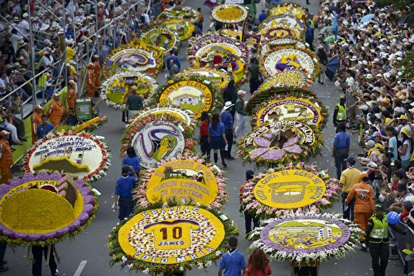 2014年8月10日,哥伦比亚鲜花节,花农们背着精心制作的花盘游行,场面壮观。(Raul ARBOLEDA/AFP)