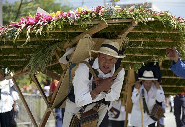 2014年8月10日,哥伦比亚鲜花节,花农们背着精心制作的花盘游行(Raul ARBOLEDA/AFP)