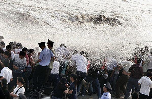 2006年10月9日,中國浙江省,錢塘觀潮的遊客都濕透了。當日錢塘江潮湧高達3.5米。 (AFP)