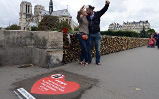 2014年8月1日,法国巴黎主教座桥上的心型标志,要求游客停止在栏杆上挂爱情锁,以自拍情侣照替代挂锁。(DOMINIQUE FAGET/AFP)