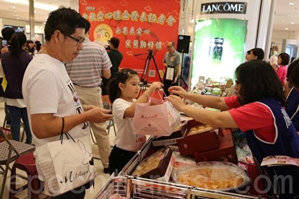 从罗东来的陈先生带着女儿现场购买蛋黄酥礼盒,支持爱心活动。(曾汉东/大纪元)