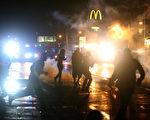 美国密州警方佛格森警民冲突,8月17日,警方朝约400名示威者施放烟雾弹,连带小孩的家庭及一旁媒体也不放过。(Joe Raedle/Getty Images)